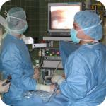 Doctors performing a laparoscopy operation on a woman